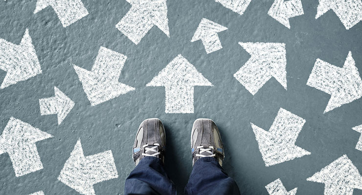 Looking down at a person's shoes, with lots of arrows going in different directions, symbolising confusion, or many options.