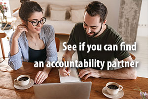 See if you can find an accountability partner. Man and woman smile over coffee, with laptop and notebook.